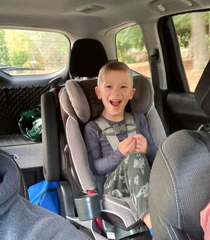 a boy smiling in a car seat