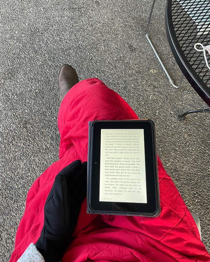 a woman reading a kindle while wrapped in a blanket