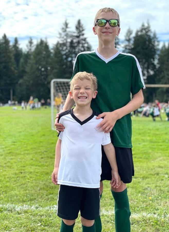 2 boys in soccer uniforms at a soccer field