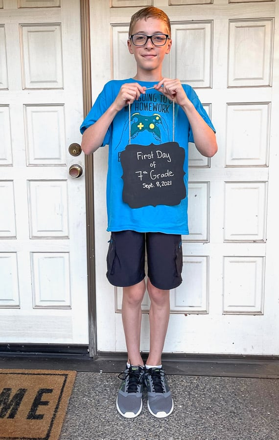 a boy in a blue shirt holding a first day of school sign