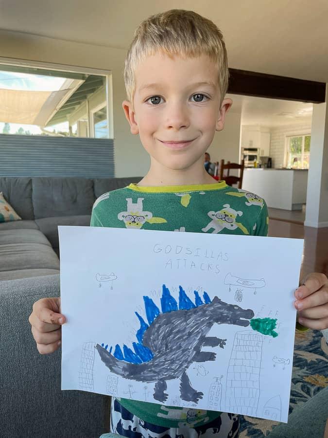 a boy holding a drawing of Godzilla