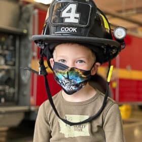 a boy in a firefighter helmet