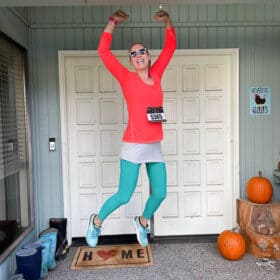 a woman in bright clothes with a race bib jumping on a front porch